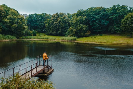Fisherman in yellow jacket standing on pier of the lake and fishing on rainy day