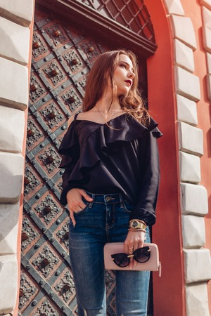 Outdoor portrait of a beautiful stylish woman in sunglasses on city street. Fashion model wearing summer clothing and accessories. Lady holding a handbag