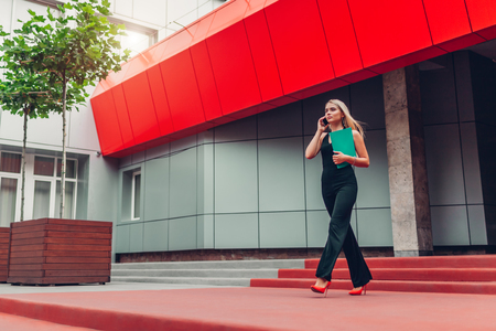 Young blonde businesswoman calling on smartphone and holding folder walking by business center in city. Business, communication, technology and people concept