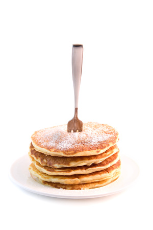 Stack of pancakes with sugar powder isolated on white background. Tasty dessert with fork stuck in it