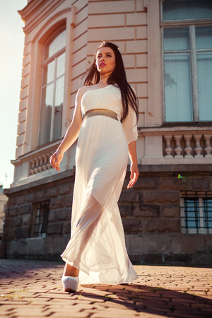 Beautiful woman walking in white wedding dress outdoors. One shoulder dress with accessories, jewellery and heels. Fashion concept