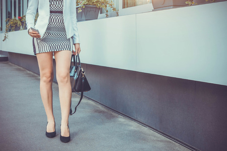 Young slim woman walking by the street using phone and wearing high heels and accessories Stock Photo