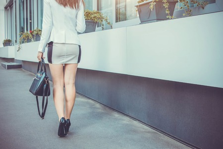 Young stylish woman walking by the street wearing high heels