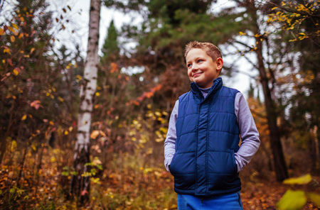 Little sportive boy having rest after exercises in autumn forest