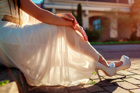 Stylish woman wearing high heeled shoes and white dress outdoors. Beauty fashion. Girl sitting with hands put on legs 免版税图像