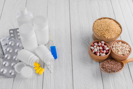 Pills or healthy eating choice. Healthy diet concept. Set of pills and cereals. Stock Photo
