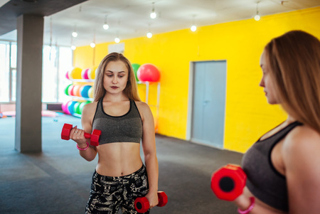 Shot of young woman exercising with dumbbells at the gym. Muscular female training in front of the mirror in the morning.