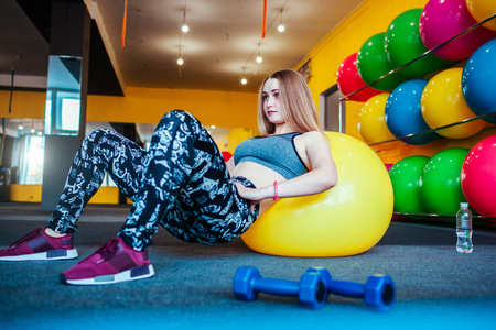 Shot of young woman exercising at the gym. Muscular female training using a ball. Woman doing sit-ups in the morning.