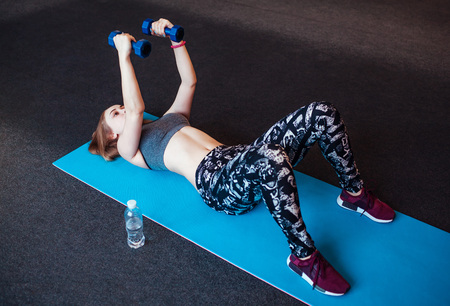 Shot of young woman exercising with dumbbells at the gym. Muscular female training on exercise mat in the morning 스톡 콘텐츠