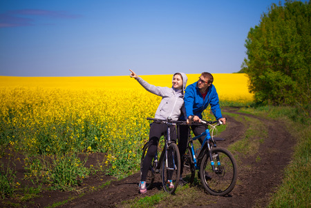 Young couple of bikers rides in spring rapeseed field Stok Fotoğraf