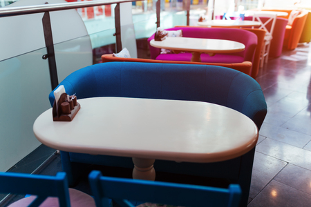 Empty cafe in shopping center. Row of colorful tables with chairs in mall. Modern interior design of restaurant Stock Photo
