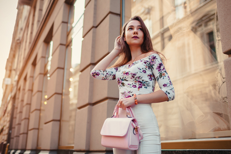 Young woman wearing beautiful outfit and accessories outdoors. Girl holding handbag. Fashion model walking in city by store showcases