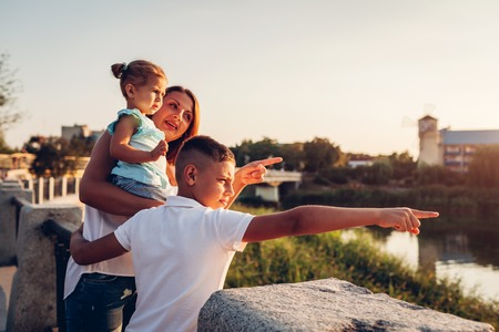 Happy family hugging and enjoying the view of river at sunset. Mother and kids pointing into the distance.