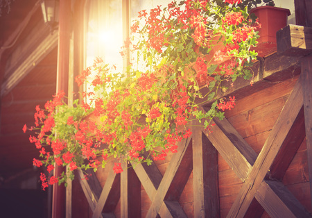 Wooden balcony with blooming geraniums. Exterior design. Decoration