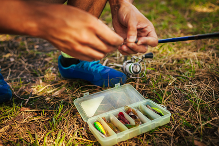 Young man attaching bait to hook of spinning. Fishing tackle. Man chooses lure in fishing gear box. Fisherman rig
