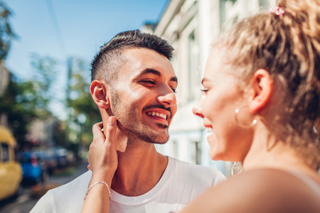 Mixed race couple in love walking in city. Arab man and his white girlfriend laughing. Young people hugging outdoors