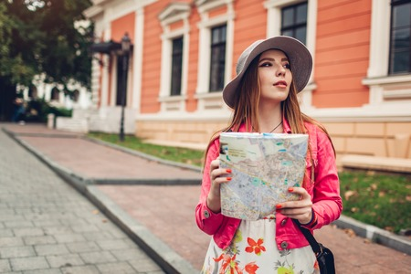 Young woman tourist searching for right way using map in Odessa, Ukraine. Girl lost in city. Traveler walking and going sightseeing