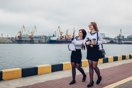 Two college women students of Marine academy walking by sea wearing uniform. Friends walking, talking and pointing into distance