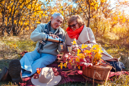 Senior couple having tea in autumn forest. Happy man and woman enjoying picnic and nature