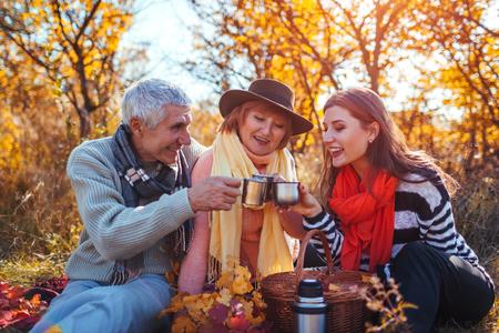 Hogere ouders die thee drinken in de herfstbos met hun dochter. Familiewaarden. Picknicken
