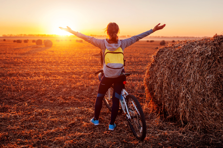 Happy young bicyclist raising opened arms in autumn field admiring the view. Woman riched destination. Free energy
