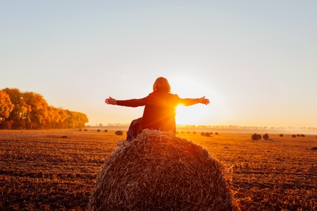 Happy middle-aged woman sitting on haystack in autumn field and feeling free with arms opened. Relaxing and admiring nature at sunset