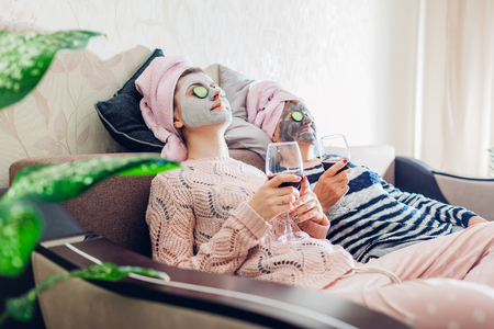 Mother and her adult daughter applied facial masks and cucumbers on eyes. Women chilling while having wine sitting on couch at home