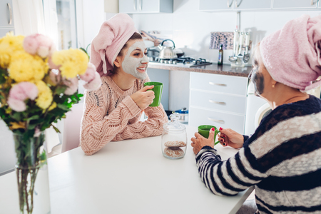 Mother and her adult daughter drinking tea with facial masks applied. Women chilling and talking on kitchen. Family values Standard-Bild