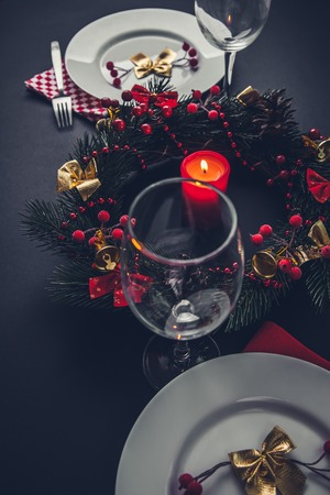 Beautiful Christmas dinner place setting for two. Table decorated with a wreath and a candle.