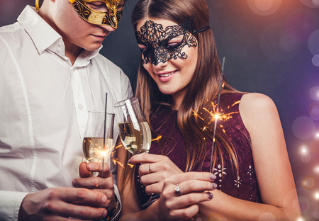 Couple celebrating New Year's eve drinking champagne and lighting up sparklers on the masquerade party Stock fotó