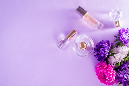 Bottles of perfume with purple and white flowers on violet background Imagens