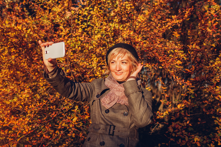 Middle-aged woman taking selfie on phone walking in park. Senior lady having fun in autumn forest