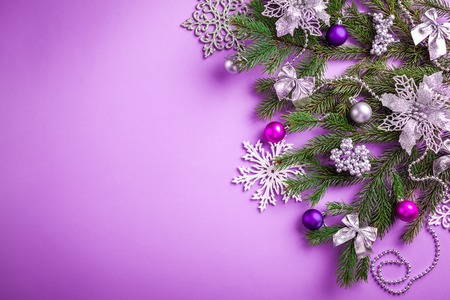 Purple Christmas and New Year background with decorated fir tree and toys. Copy space Stock Photo