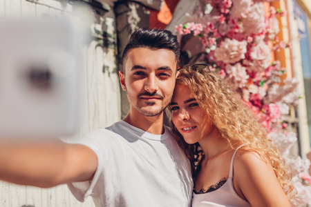 Mixed race couple in love taking selfie on smartphone walking in city. Happy arab man and white woman on date
