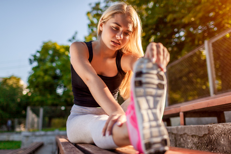 Young woman athlete warming up before running on sportsground in summer. Stretching body. Doing morning exercises Imagens