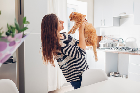 Young woman playing with cat in kitchen at home. Girl holding and raising red cat. Happy master having fun with her pet