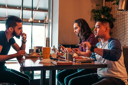 Multiracial friends eat breakfast in cafe. Young arabic men chat while having tasty food and drinks. Guys hangout together