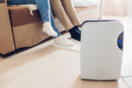 Dehumidifier with touch panel, humidity indicator, uv lamp, air ionizer, water container works in apartment while people relaxing. Close up