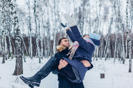 Guy carrying his girlfriend on hands in winter forest while she throwing snow. Happy people having fun outdoors