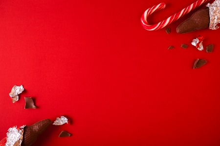 Christmas traditional sweets on red background. Chocolate Santa Clauses with candy cane. Copy space