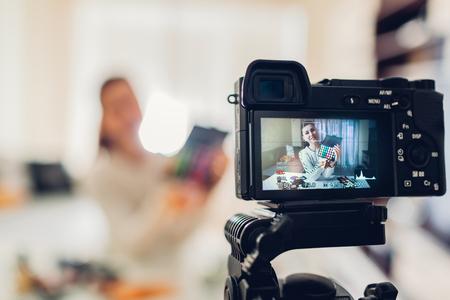 Giovane donna professionale vlogger di bellezza o blogger registrazione make up tutorial utilizzando la fotocamera e il treppiede a casa Archivio Fotografico