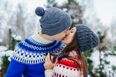Young couple drinking tea and kissing in winter forest. Happy people relaxing outdoors during holidays. Valentines day Stock Photo
