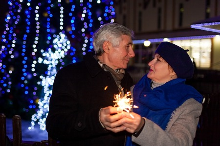 Senior family couple burning sparklers by holiday illumination at night. Christmas and New year concept 스톡 콘텐츠