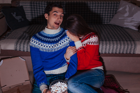 Young couple watching horror movie eating popcorn at home at night