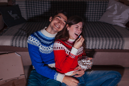 Young couple watching comedy movie eating popcorn at home at night. Family laughing