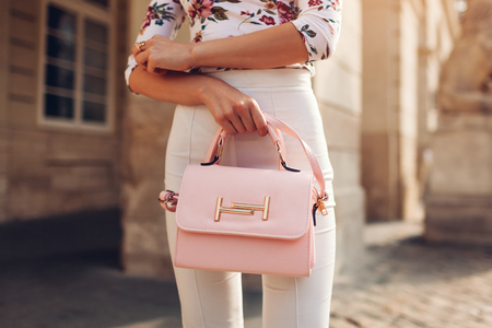 Close-up of stylish female handbag. Young woman wearing beautiful outfit and accessories outdoors on city street. City fashion