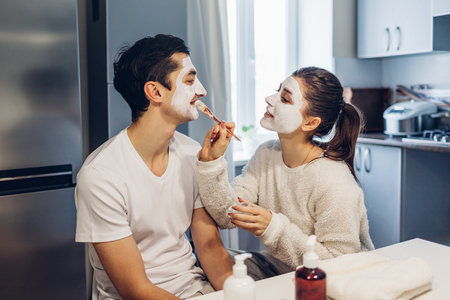 Woman applying clay mask on her boyfriends face. Young loving couple taking care of skin at home 版權商用圖片