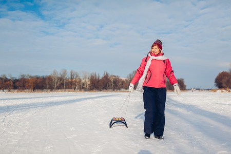 Senior woman carrying sleigh after sledding down. Woman having fun on winter frozen river. Active lifestyle