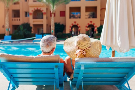 Senior couple relaxing by swimming pool. People enjoying vacation. Valentines day
