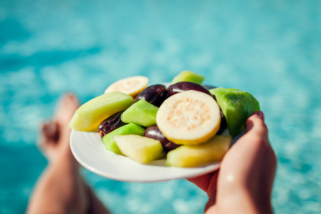 Woman holds plate with fruits on swimming pool background.